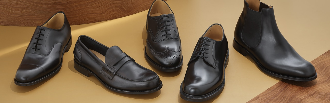 A selection of Church's black leather iconic shoes and boots against wooden background