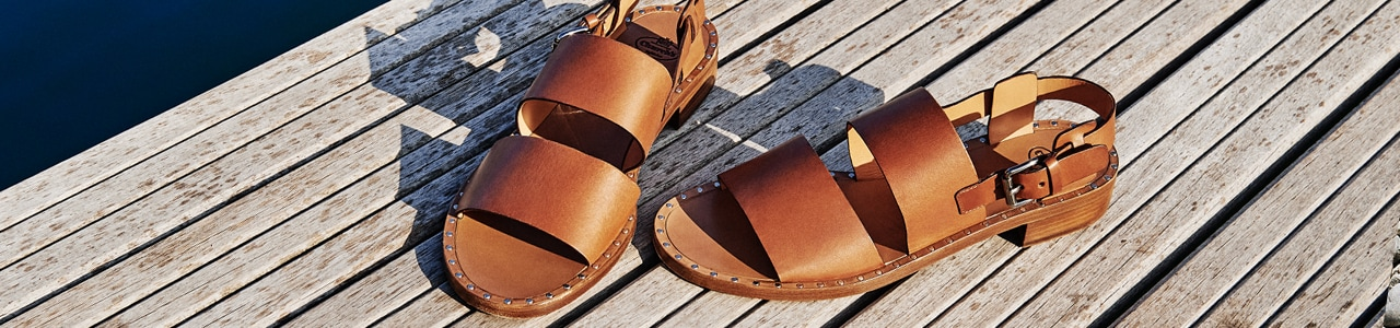 Women's brown leather sandals with silver buckle on decking