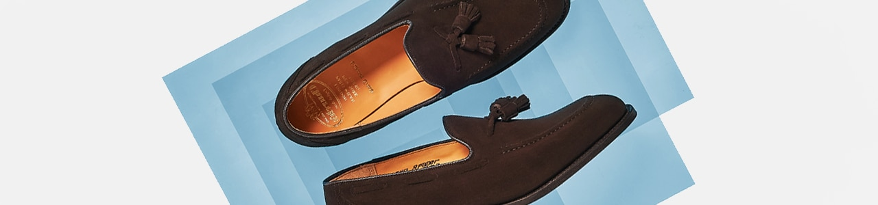 Brown suede loafers on blue background