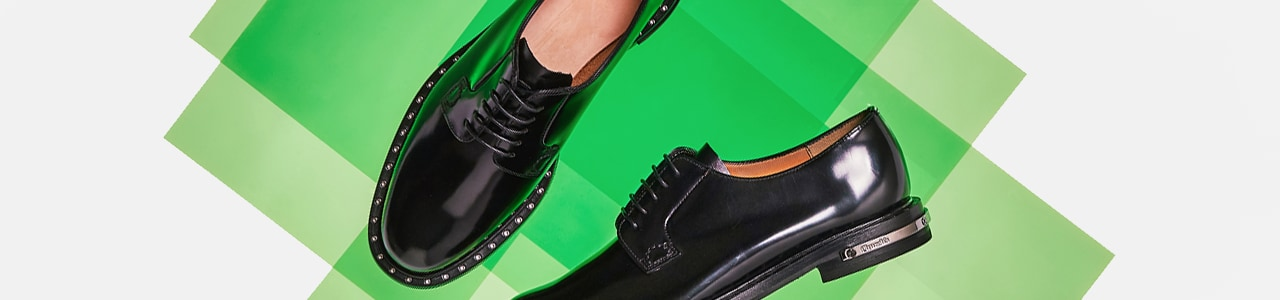 Women's black leather lace ups with stud detailing against green background